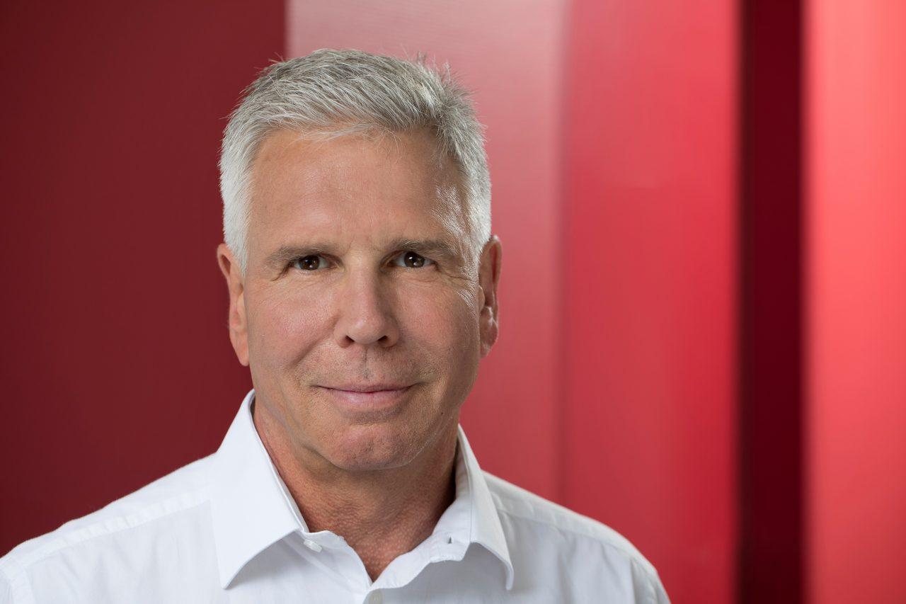 Dr. med. Dirk Meyer-Rogge mit weißem Hemd vor rotem Hintergrund.