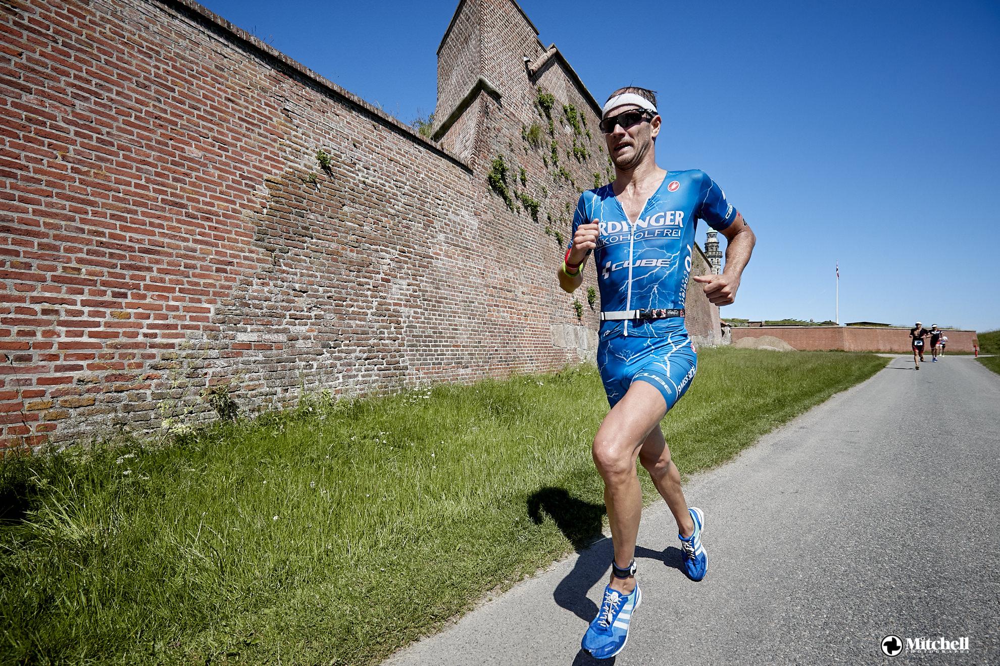 Triathlet läuft im blauen Triathlon-Einteiler.