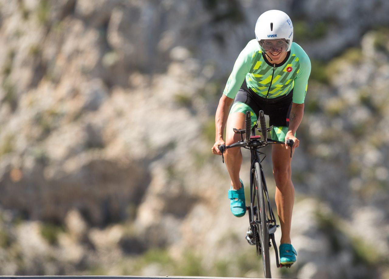 Triathletin Laura Philipp fährt Rennrad und trägt einen grünen Einteiler.