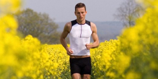 Mann trägt Triathlon-Anzug auf gelbem Rapsfeld