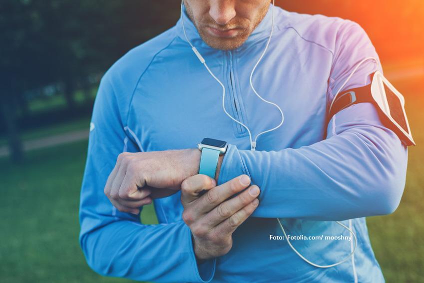 Mann in Sportklamotten gekleidet schaut auf seine Smart-Watch.