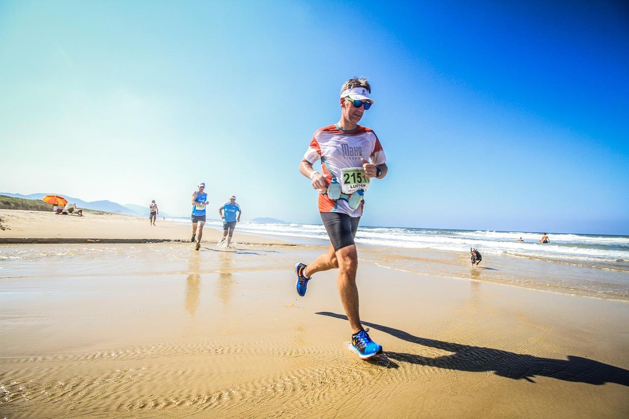Ein Triathlet beim Laufen an einem Strand bei schönem Wetter.